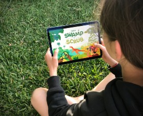 A school student viewing the 'From Swamp to Scrub' online National Science Week presentation on a mobile device.